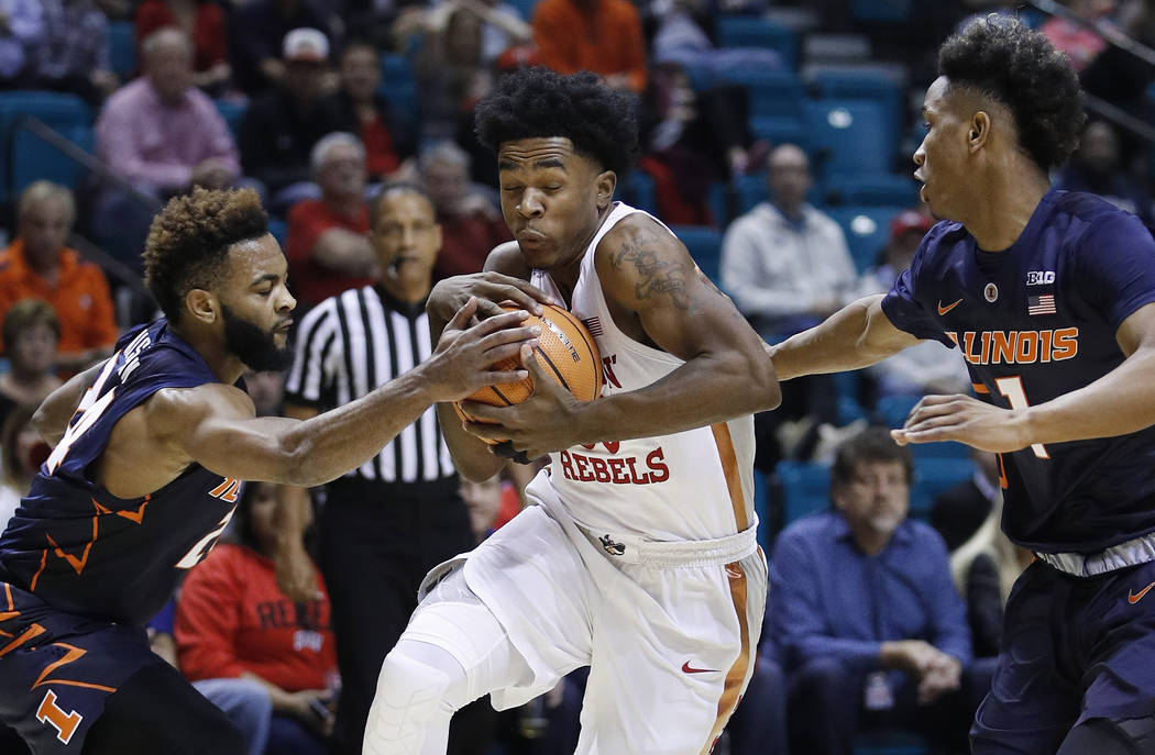 UNLV's Jovan Mooring, center, drives between Illinois' Mark Alstork, left, and Trent Frazier during the first half of an NCAA college basketball game Saturday, Dec. 9, 2017, in Las Vegas. (AP Phot ...
