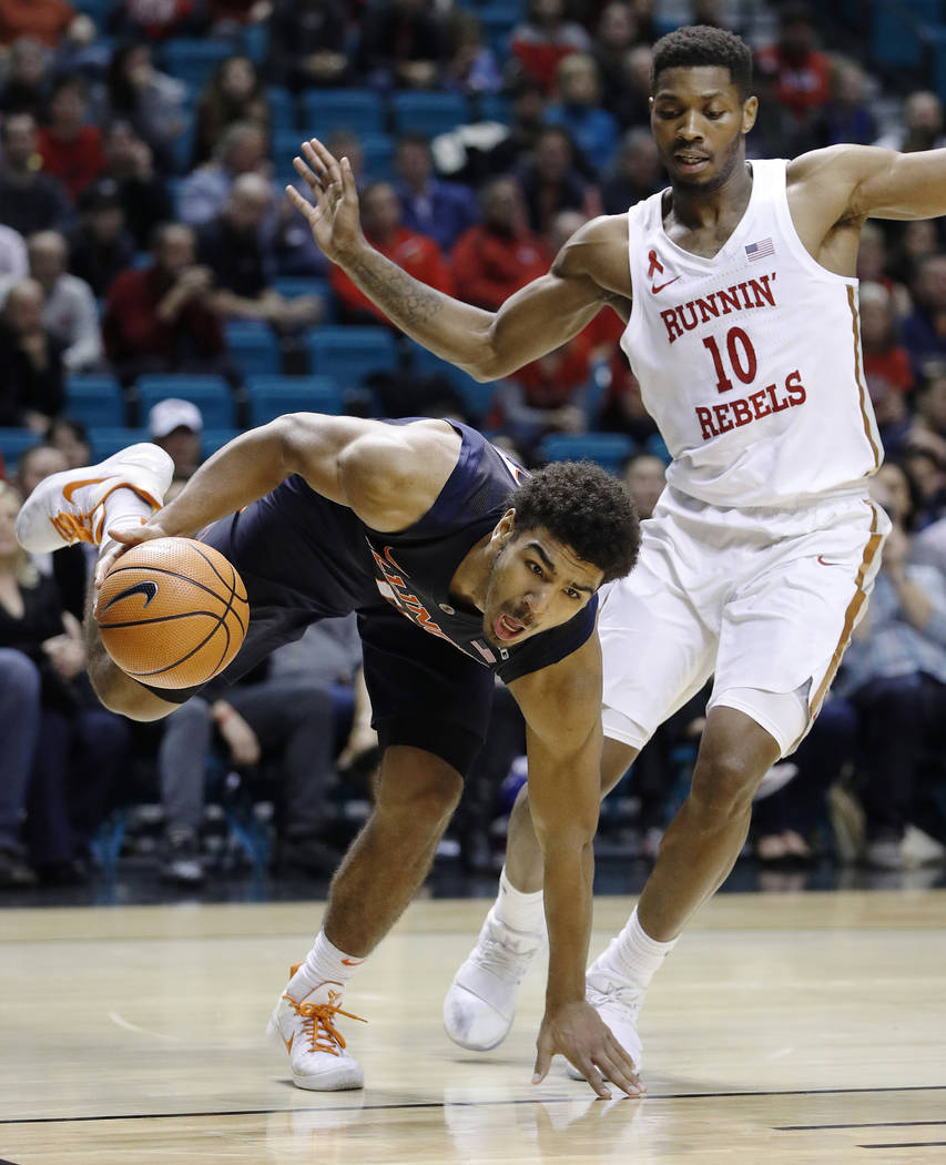 Illinois' Mark Smith drives around UNLV's Shakur Juiston during the second half of an NCAA college basketball game Saturday, Dec. 9, 2017, in Las Vegas. (AP Photo/John Locher)