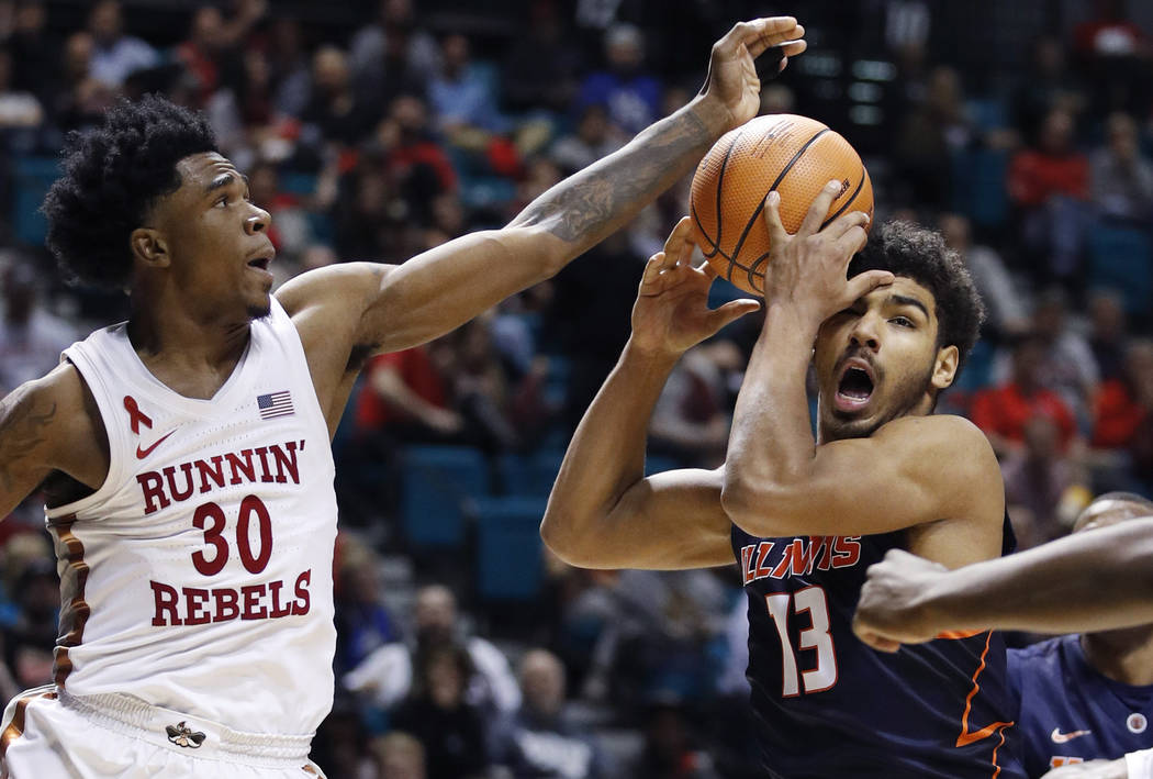Illinois' Mark Smith, right, grabs a rebound over UNLV's Jovan Mooring during the second half of an NCAA college basketball game Saturday, Dec. 9, 2017, in Las Vegas. (AP Photo/John Locher)