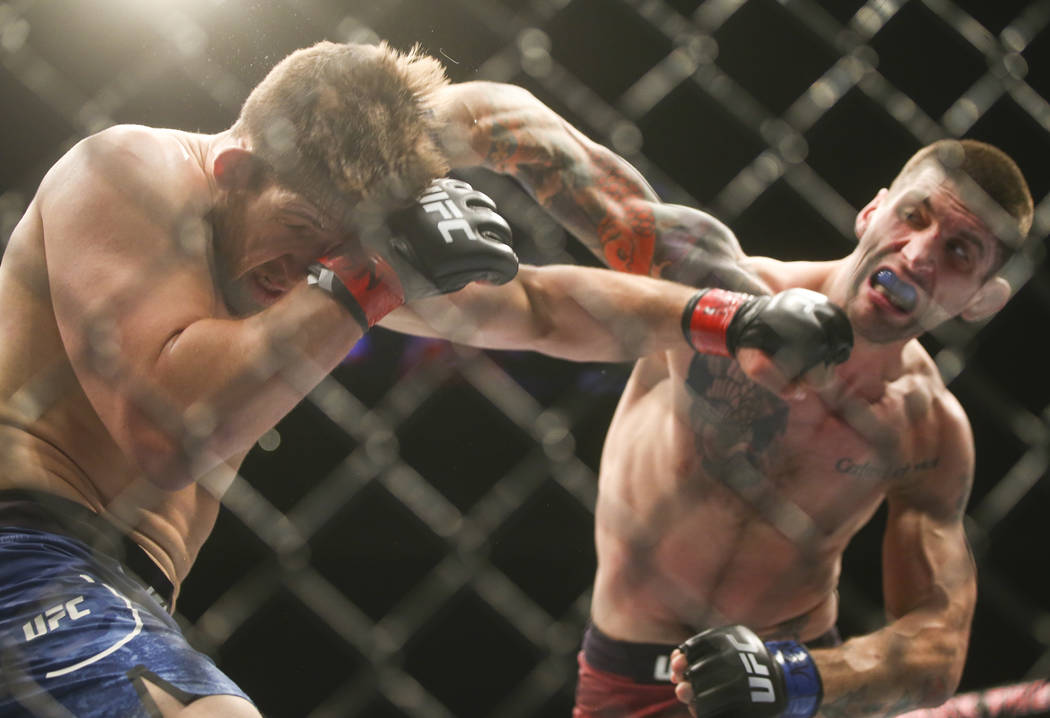 """Andrew Sanchez, left, takes a hit from Ryan Janes in their middleweight bout during """"The Ultimate Fighter""""Season 26 Finale card at the Park Theater at Monte Carlo in  ..."""
