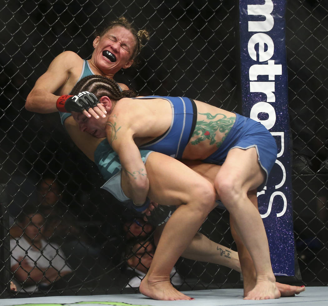 Lauren Murphy, right, keeps Barb Honchak against the octagon during a women's flyweight bout at the Park Theater at Monte Carlo in Las Vegas on Friday, Dec. 1, 2017. Murphy won via split decision. ...