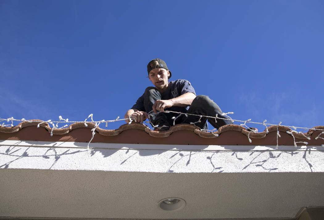Tyler Tadman, a worker with Spotless Residential Services, installs Christmas lights on the roof of a private residence in the Summerlin area of Las Vegas on Wednesday, Nov. 29, 2017. Richard Bria ...