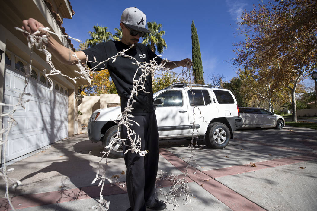Jeff Lark, a worker with Spotless Residential Services, untangles a batch of Christmas lights before installing them on a private residence in the Summerlin area of Las Vegas on Wednesday, Nov. 29 ...
