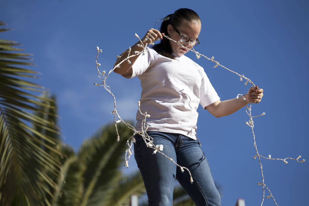 Megan Espejo, a worker with Spotless Residential Services, installs Christmas lights on the roof of a private residence in the Summerlin area of Las Vegas on Wednesday, Nov. 29, 2017. Richard Bria ...