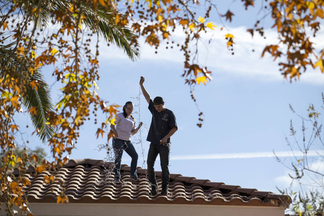 Tyler Tadman and Megan Espejo, workers with Spotless Residential Services, install Christmas lights on the roof of a private residence in the Summerlin area of Las Vegas on Wednesday, Nov. 29, 201 ...