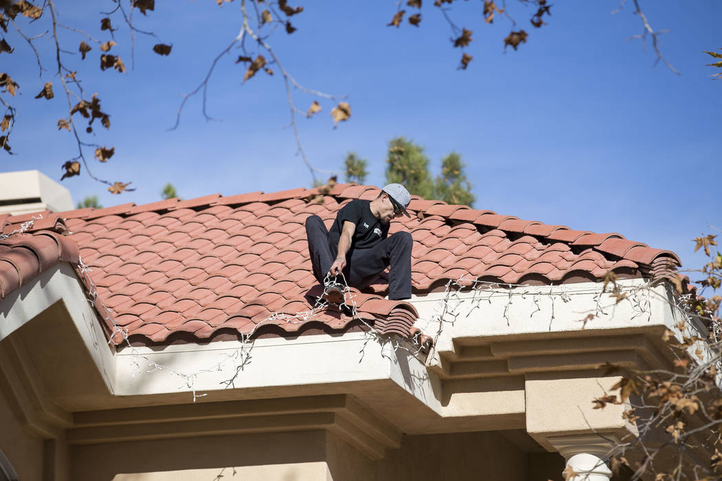 Jeff Lark, a worker with Spotless Residential Services, installs Christmas lights on the roof of a private residence in the Summerlin area of Las Vegas on Wednesday, Nov. 29, 2017. Richard Brian L ...