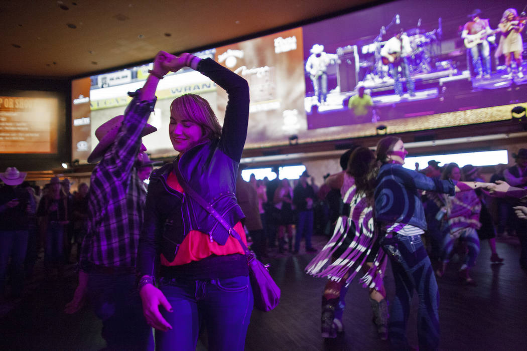 Melanie Arnold and Grant Huber dance to live music by Chancey Williams and the Younger Brothers Band at the Race & Sportsbook at the Mirage in Las Vegas. (Rachel Aston/Las Vegas Review-Journal ...