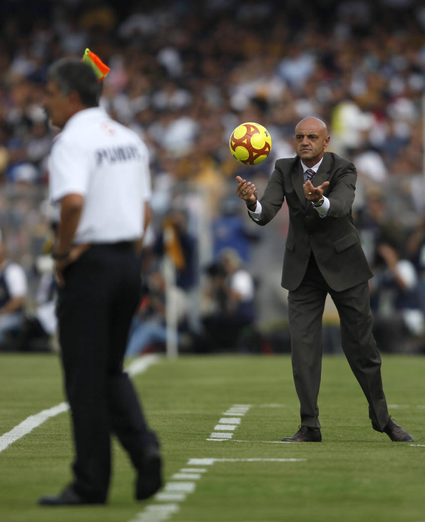 Puebla's coach Jose Luis Sanchez Sola, right, throws the ball as Pumas' coach Ricardo Feretti looks on during a Mexican soccer league match in Mexico City, Saturday May 23, 2009. (AP Photo/Claudio ...