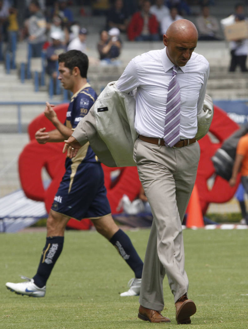 Puebla's  coach Jose Sola leaves the field at the end of the first half during a Mexico's league soccer game against Pumas in Mexico City, Sunday, March 7, 2010. Pumas won 4-1. (AP Photo/Daniel Jayo)