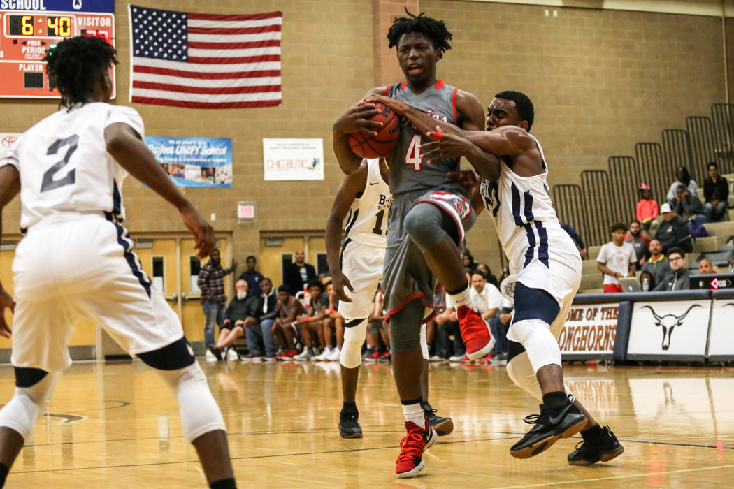 Arbor View's Tyre Williams (4), center, is guarded by Democracy Prep's Daniel Plummer (30), right, during the second quarter of the Legacy Tip-Off Classic basketball tournament quarterfinals at Le ...