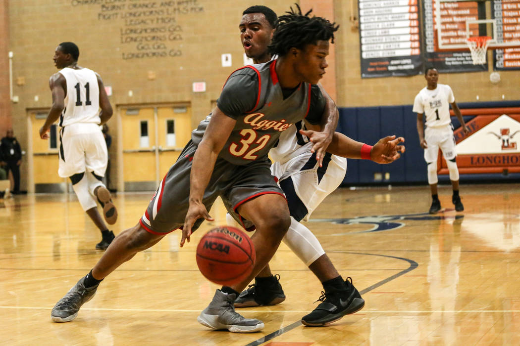 Arbor View's Jeremiah Wade (32), left, is guarded by Democracy Prep's Daniel Plummer (30), right, during the third quarter of the Legacy Tip-Off Classic basketball tournament quarterfinals at Lega ...