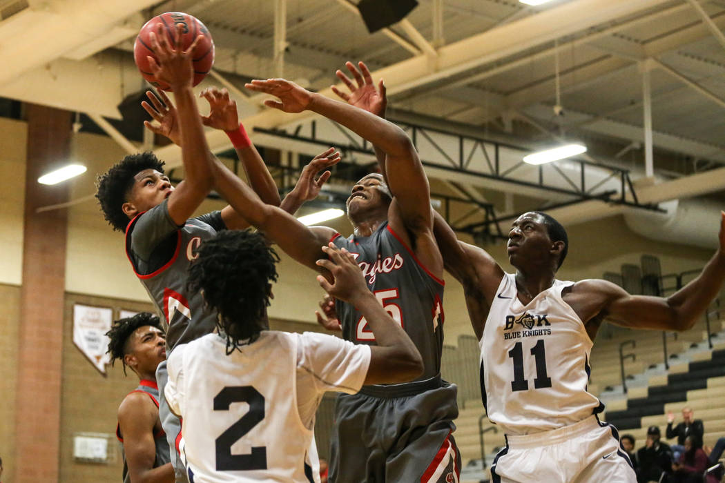 Arbor View's Donovan Yap (0), top left, receives a rebound as his teammate Jarrod Burks (25) and  Democracy Prep's  Akeemis Williams (2) and Jared Holmes (11) struggle during the fourth quarter of ...
