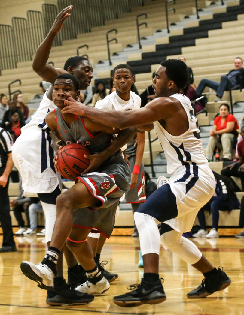 Arbor View's Favor Chukwukelu (2), center, runs the ball as he is guarded by Democracy Prep's Daniel Plummer (30), right, during the fourth quarter of the Legacy Tip-Off Classic basketball tournam ...