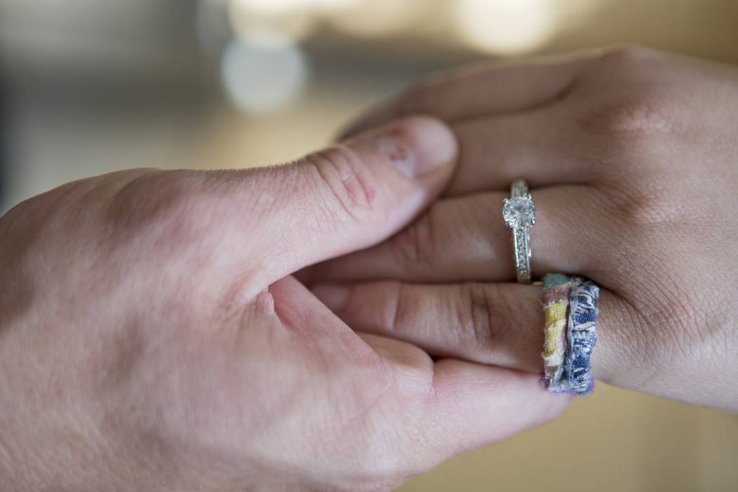 William King, left, hold's Kimberly Calderon's hand with her engagement rings in their home in Las Vegas, Wednesday, Dec. 13, 2017. The ring on Calderon's pinky finger was made by King out of the  ...