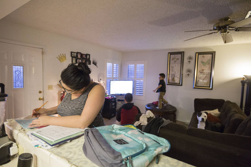 Kimberly Calderon, left, checks her daughter's homework while her kids play video games in their home, Wednesday, Dec. 6, 2017 in Las Vegas. Elizabeth Brumley Las Vegas Review-Journal  @EliPagePhoto