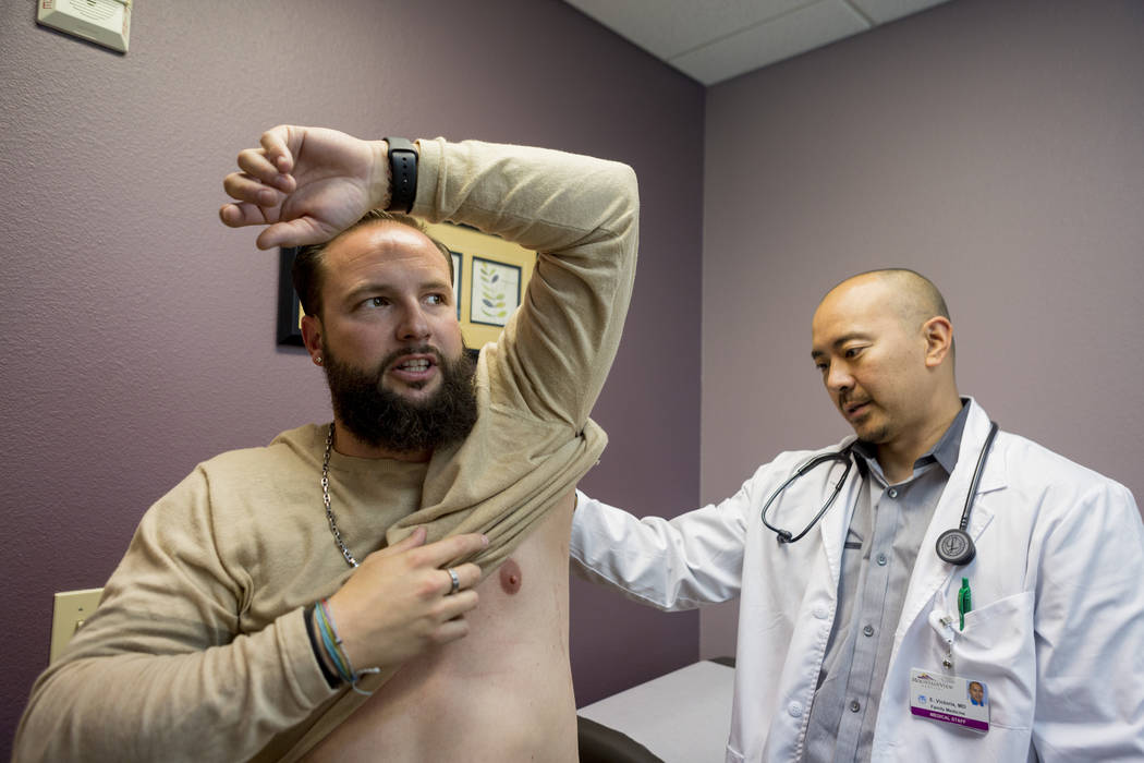 William King, left, holds up his arm while Dr. Edward S. Victoria examines King's bullet wound from the Route 91 Harvest festival shooting, in Dr. Victoria's clinic in Las Vegas, Thursday, Nov. 30 ...