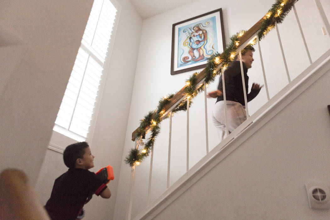 Maximus Calderon, 6, chases Eli King, 8, up the stairs with their gifts given to them by Central Church, Wednesday, Dec. 6, 2017 in Las Vegas. Elizabeth Brumley Las Vegas Review-Journal  @EliPagePhoto