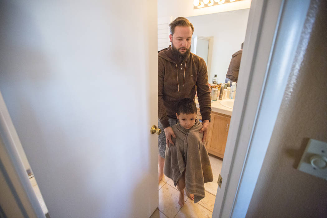 Maximus Calderon, 6, gets ready for school with the help of his dad William King in their home Friday morning, Dec. 8, 2017 while they get ready for school, in Las Vegas. Elizabeth Brumley Las Veg ...