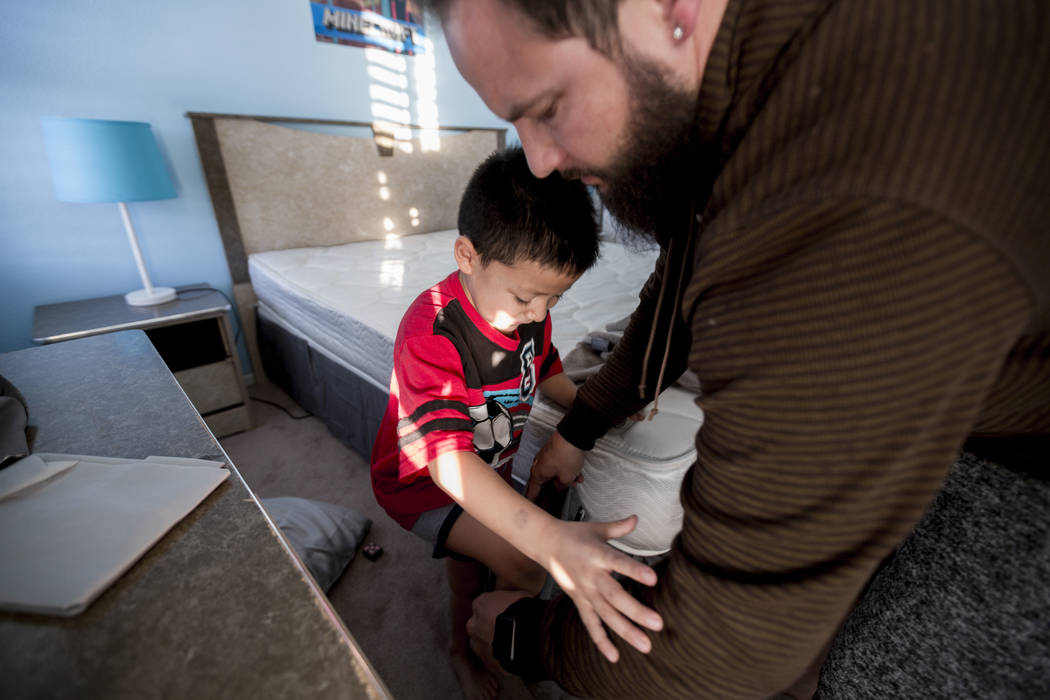 Maximus Calderon, 6, puts on pants with the help of his dad William King in their Las Vegas home Friday morning, Dec. 8, 2017, while they get ready for school. Elizabeth Brumley Las Vegas Review-J ...