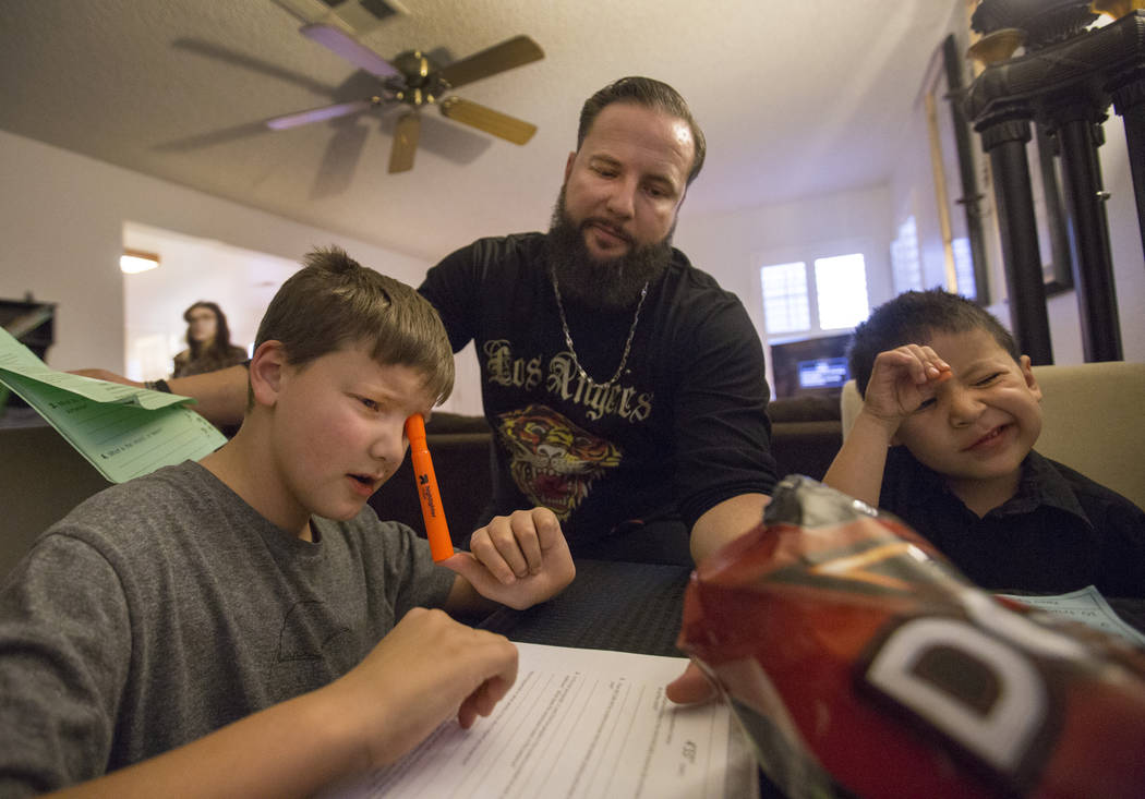Enoch king, 9, left, William King, and Maximus Calderon, 6, works on homework in their Las Vegas home Wednesday Dec. 6, 2017. Elizabeth Brumley Las Vegas Review-Journal  @EliPagePhoto