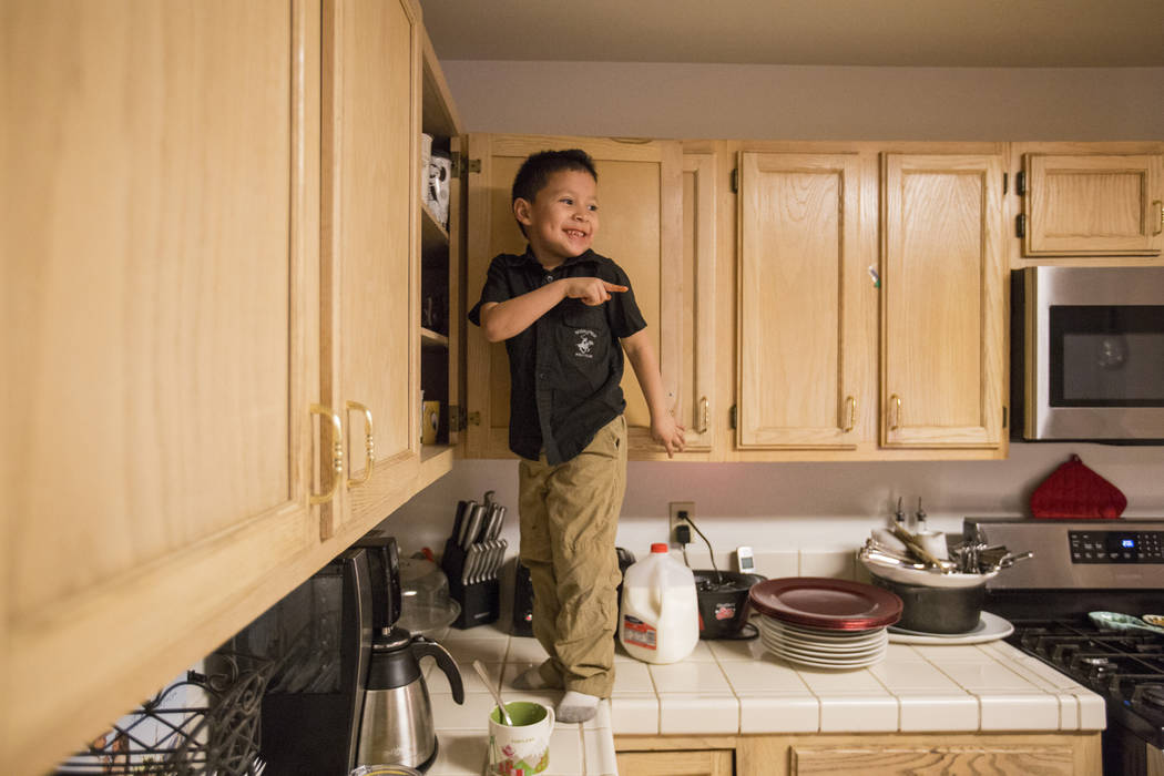 Maximus Calderon, 6, takes a break from homework to get his own cup of milk before his mom caught him and told him to get down, in their Las Vegas home Wednesday Dec. 6, 2017. Elizabeth Brumley La ...