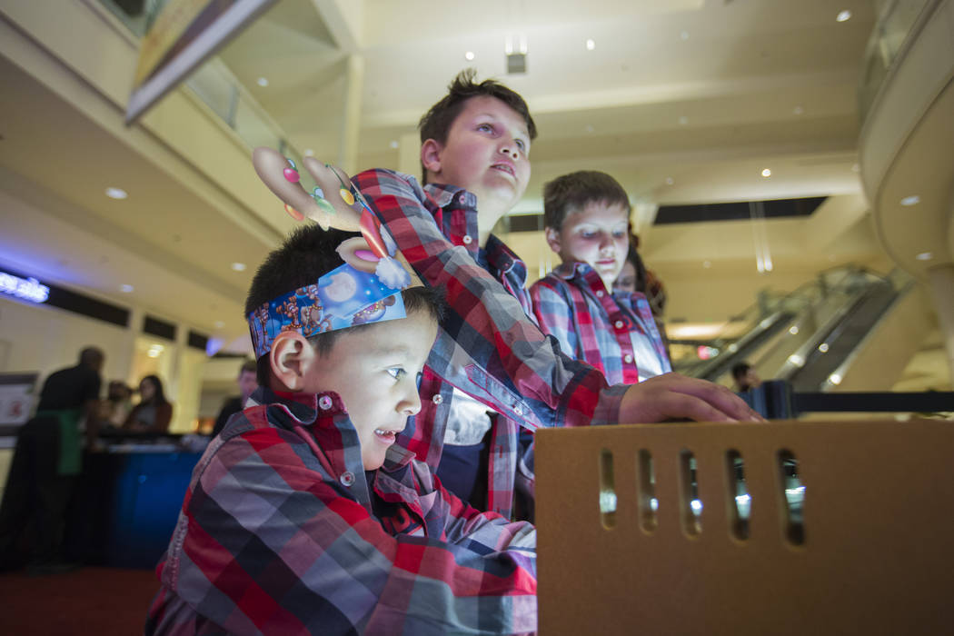 Maximus Calderon, 6, from left, Eli king, 8, Enoch King, 9, play the keyboard that makes the lights on the Christmas trees change with the note played at Fashion Show Mall in Las Vegas Wednesday,  ...