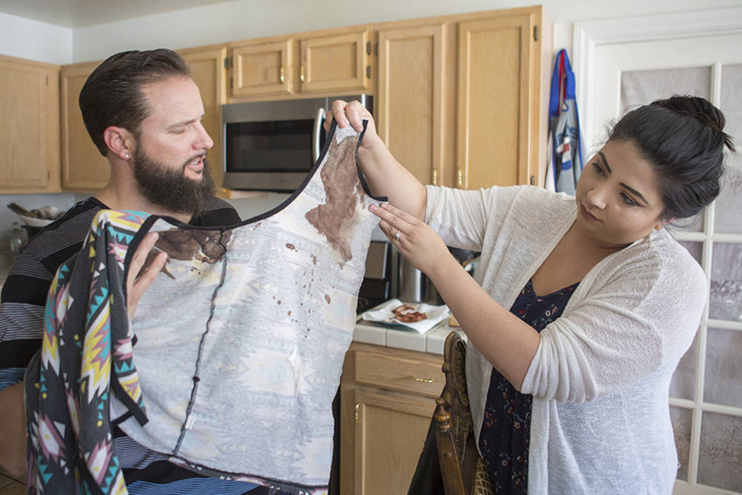 William King and Kimberly Calderon, hold shirts in their Las Vegas home Wednesday, Dec. 13, 2017, that they wore Oct. 1, 2017, during the Route 91 Harvest festival shooting where King was shot in  ...