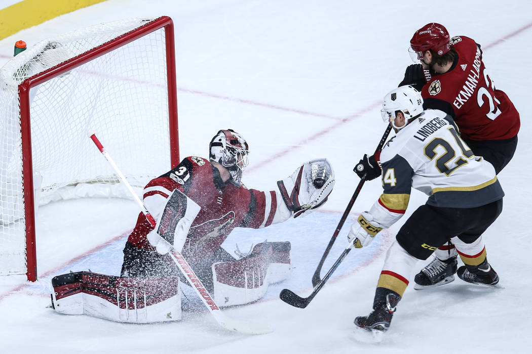 Arizona Coyotes goalie Scott Wedgewood (31), left, blocks a shot from Vegas Golden Knights center Oscar Lindberg (24), center, as he is guarded by Arizona Coyotes goalie Antti Raanta (32), right,  ...