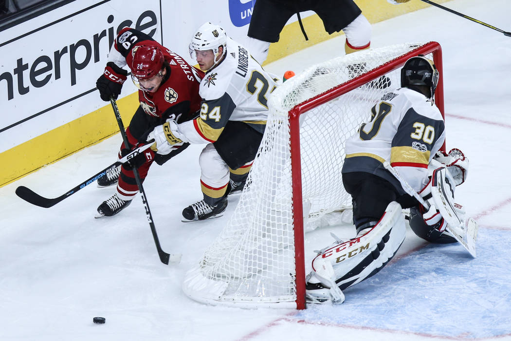 Arizona Coyotes Dylan Strome (20), left, and Vegas Golden Knights center Oscar Lindberg (24), center, chase after the puck as Vegas Golden Knights goalie Malcolm Subban (30), right, guards the goa ...