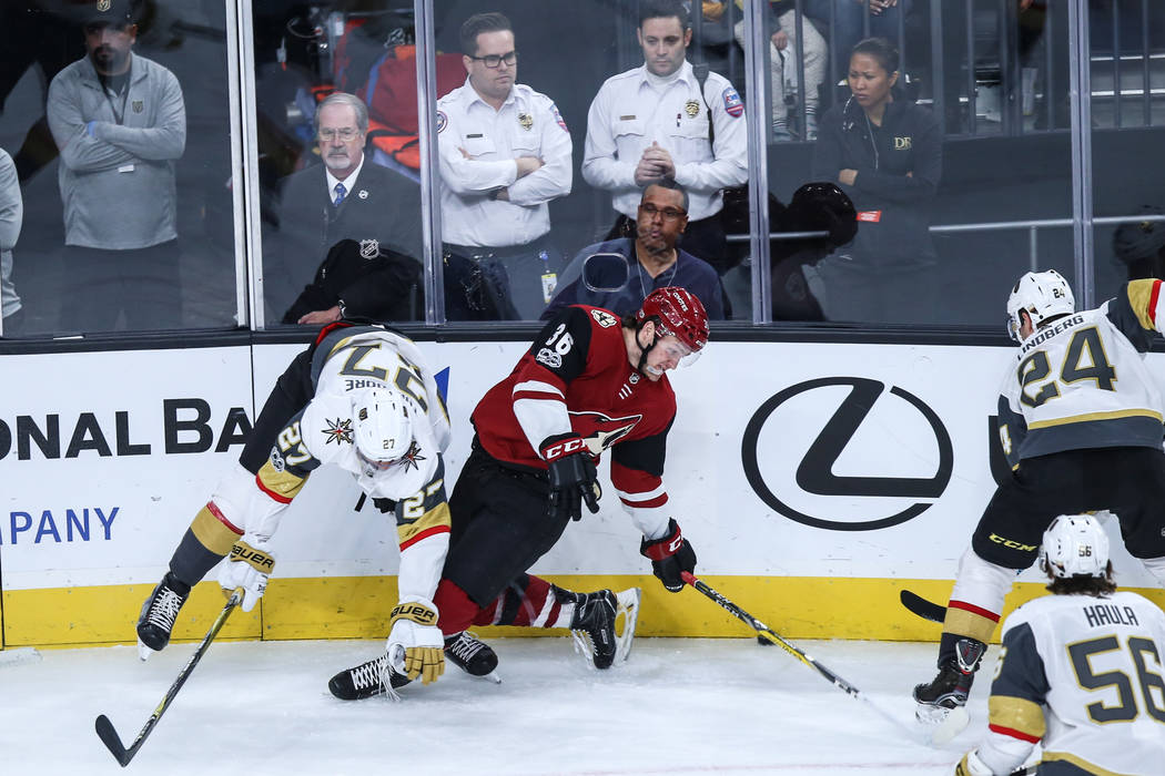 Vegas Golden Knights' Shea Theodore (27), left, and Arizona Coyotes right wing Christian Fischer (36), right, collide during the second period of a hockey game at T-Mobile Arena in Las Vegas, Sund ...