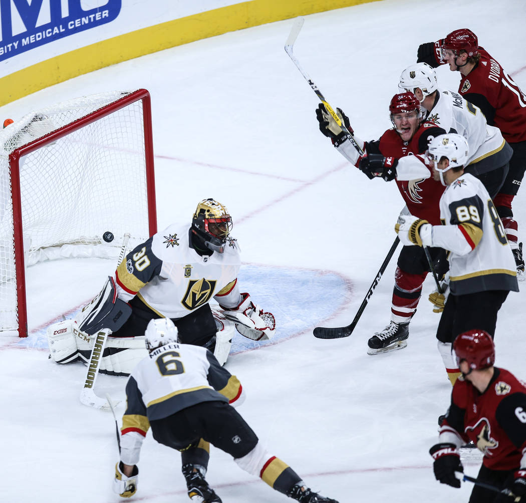 Arizona Coyotes defenseman Jakob Chychrun (6), bottom right, scores on Vegas Golden Knights goalie Malcolm Subban (30), left, during the second period of a hockey game at T-Mobile Arena in Las Veg ...