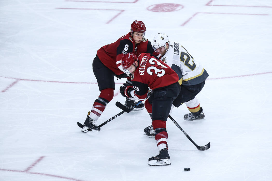 Arizona Coyotes defenseman Jakob Chychrun (6), left, Arizona Coyotes defenseman Alex Goligoski (33), center, and Vegas Golden Knights center Oscar Lindberg (24), right, stare at the puck during th ...