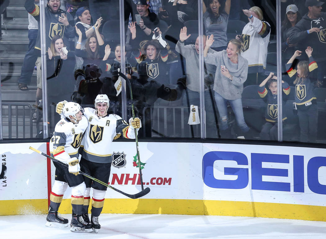 Vegas Golden Knights Shea Theodore (27), left, congratulates teammate Reilly Smith (19), right, after scoring the game-winning goal against the Arizona Coyotes during overtime of a hockey game at  ...