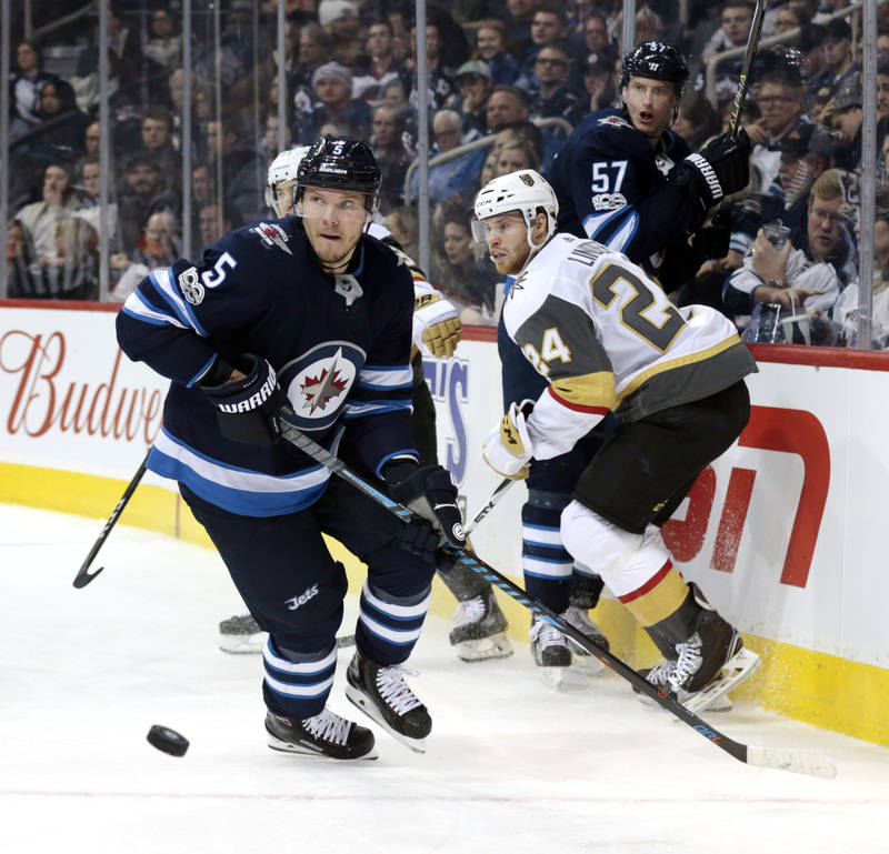 Dec 1, 2017; Winnipeg, Manitoba, CAN;  Winnipeg Jets defenseman Dmitry Kulikov (5) chases a lose puck in the third period from Vegas Golden Knights center Oscar Lindberg (24) at Bell MTS Place. Ma ...