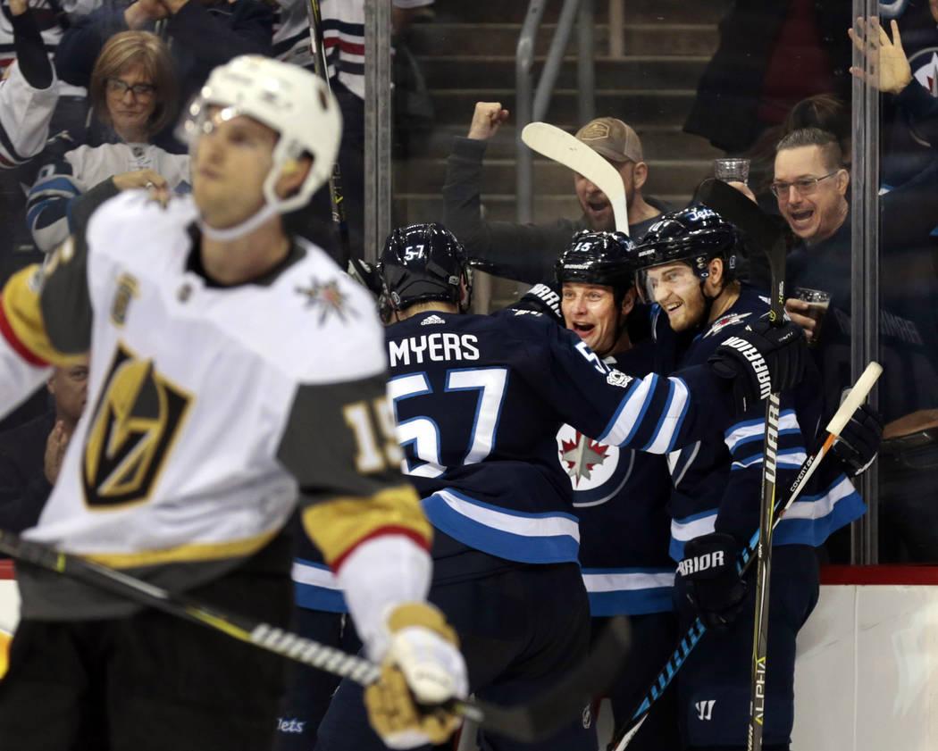 Dec 1, 2017; Winnipeg, Manitoba, CAN;  Vegas Golden Knights defenseman Jon Merrill (15) skates pass Winnipeg Jets players celebrating Winnipeg Jets center Matt Hendricks (15) second period goal at ...