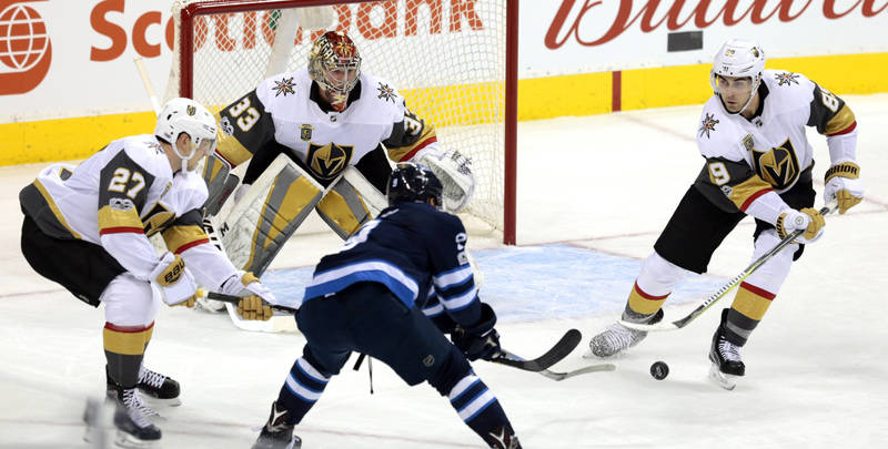 Dec 1, 2017; Winnipeg, Manitoba, CAN;  Vegas Golden Knights right wing Alex Tuch (89) keeps the puck away from Winnipeg Jets center Andrew Copp (9) during first period play at Bell MTS Place. Mand ...