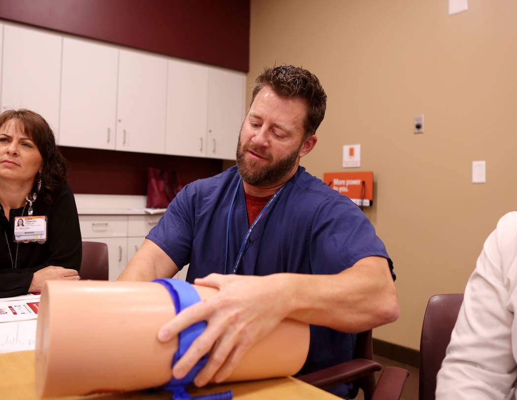 Physician Daniel Blake practices the correct way to stop bleeding during a training by University Medical Center personnel for St. Rose Dominican Hospital and Henderson officials at the St. Rose S ...