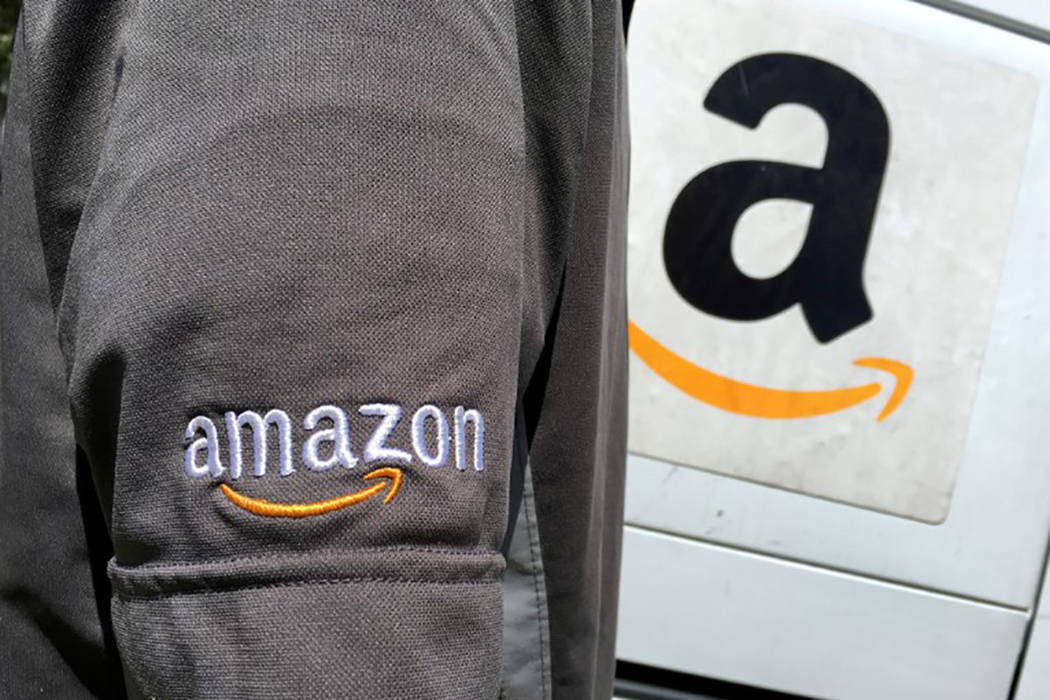 An Amazon.com Inc driver stands next to an Amazon delivery truck in Los Angeles. (REUTERS/Lucy Nicholson)
