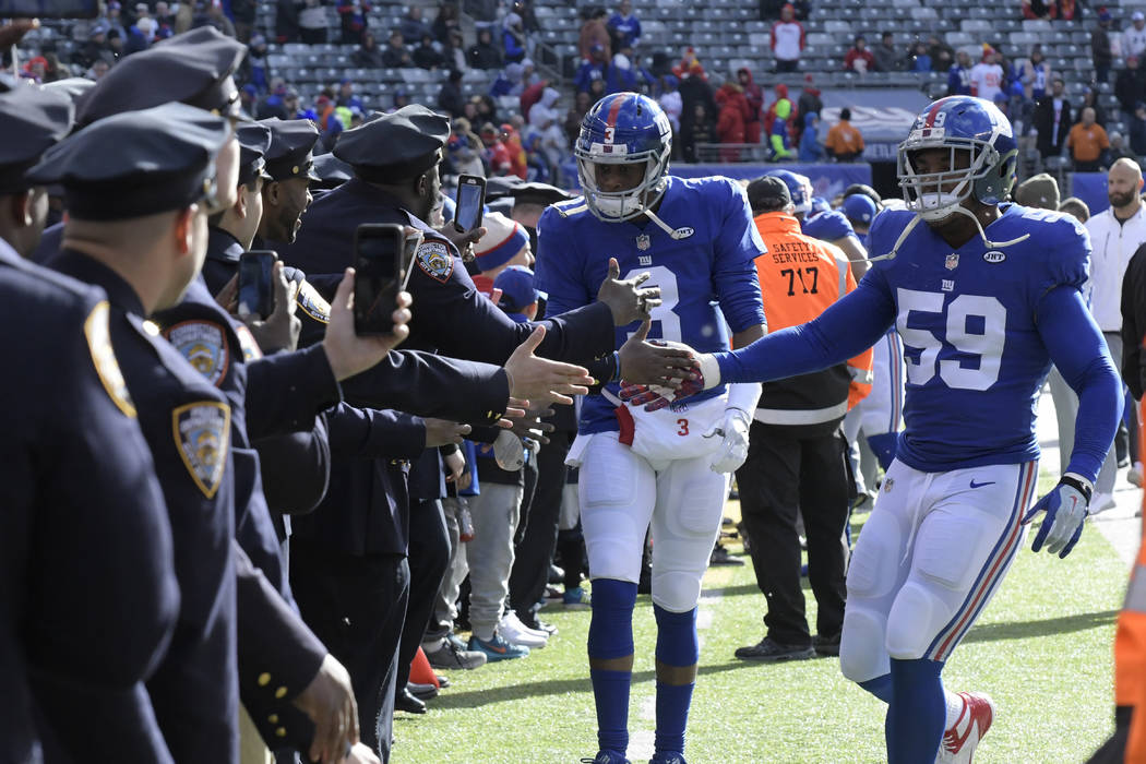 New York Giants quarterback Geno Smith (3) and linebacker Devon Kennard (59) greet New York City police officers before an NFL football game against the Kansas City Chiefs Sunday, Nov. 19, 2017, i ...