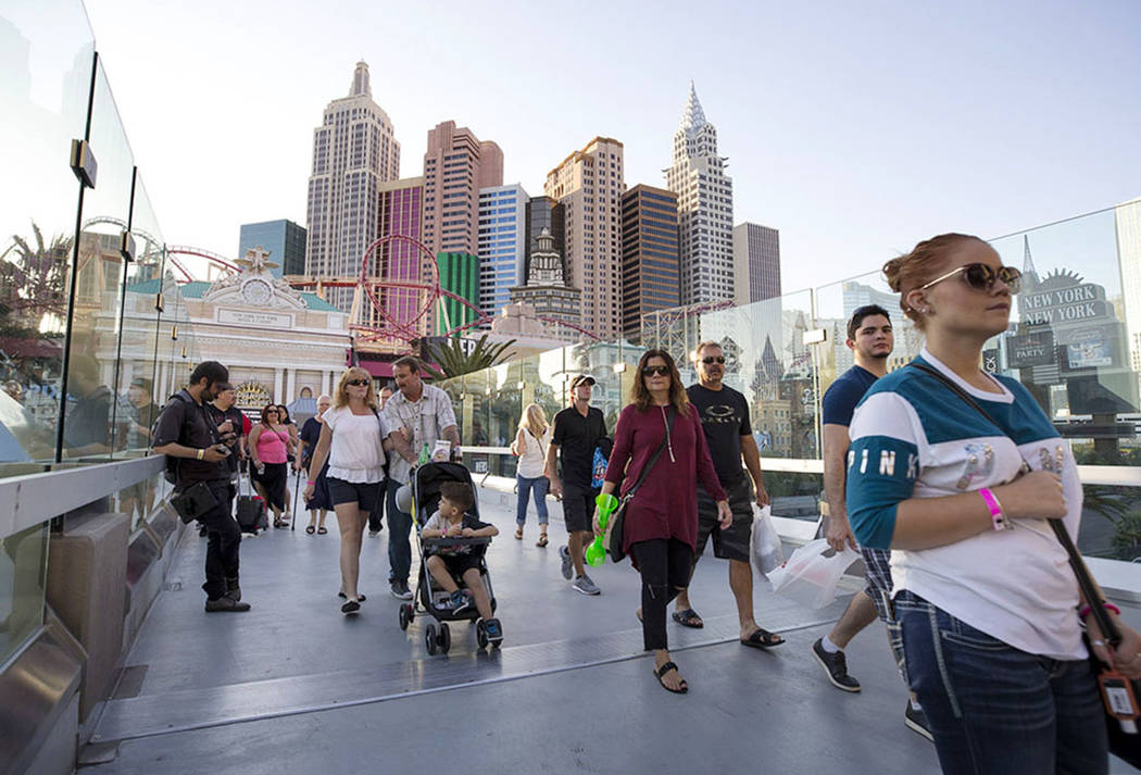 People walk over a pedestrian bridge linking New York-New York and MGM Grand near the intersection of Las Vegas Boulevard and Tropicana Avenue in Las Vegas, Thursday, Oct. 12, 2017. Richard Brian  ...