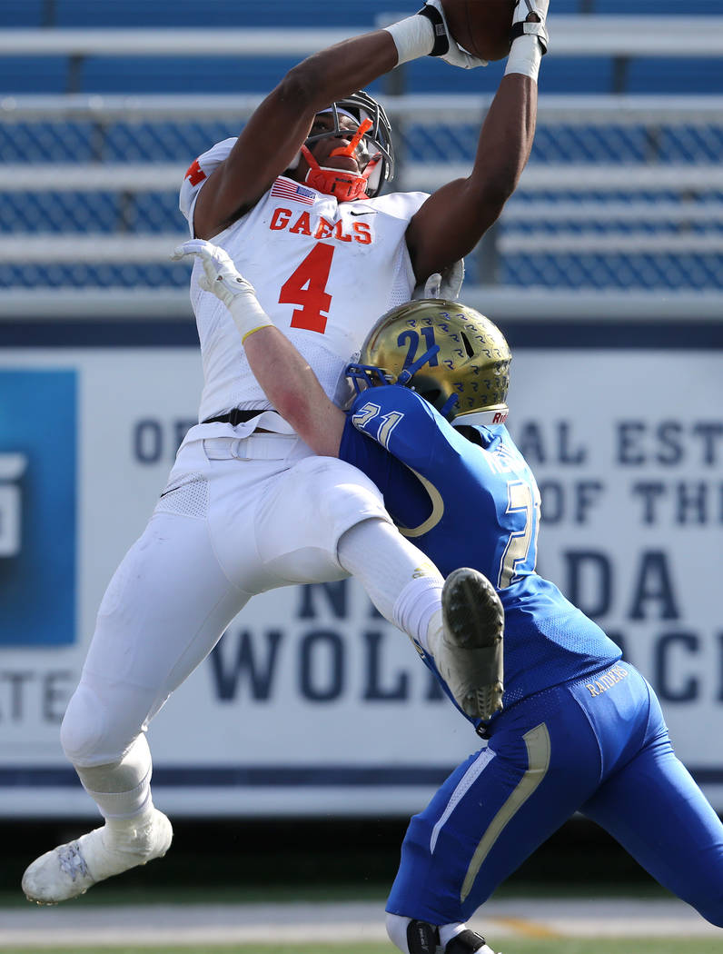 Bishop Gorman's Cedric Tillman goes up for a reception against Reed's Chase Merrill during the first half of the NIAA 4A state championship football game in Reno, Nev., on Saturday,  ...