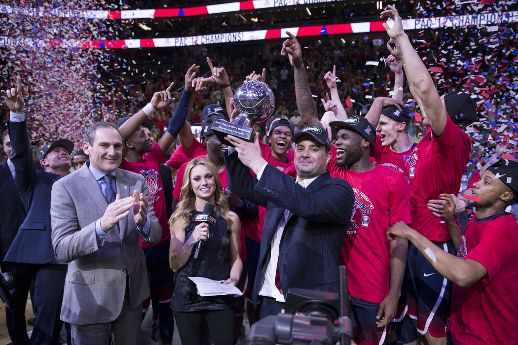 Arizona Wildcats head coach Sean Miller holds up the trophy after his team's win against Oregon Ducks in an NCAA college basketball game for the Pac-12 tournament championship at T-Mobile Arena Sa ...