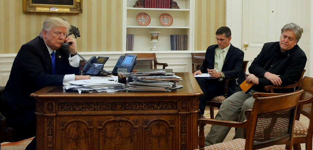 President Donald Trump, left, is seated at his desk with then National Security Advisor Michael Flynn and senior advisor Steve Bannon, Jan. 28, 2017. (Jonathan Ernst/Reuters, File)