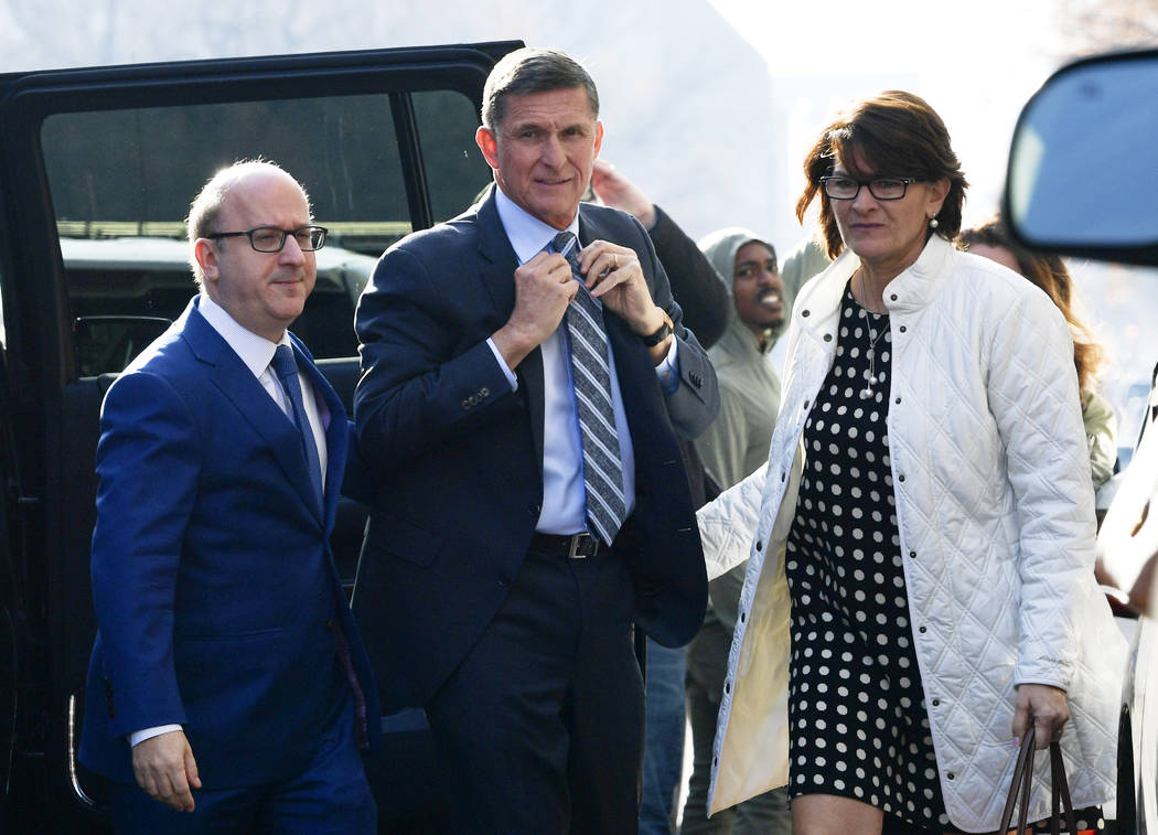 Former Trump national security adviser Michael Flynn, center, arrives at federal court in Washington, Friday, Dec. 1, 2017. Court documents show Flynn, an early and vocal supporter on the campaign ...