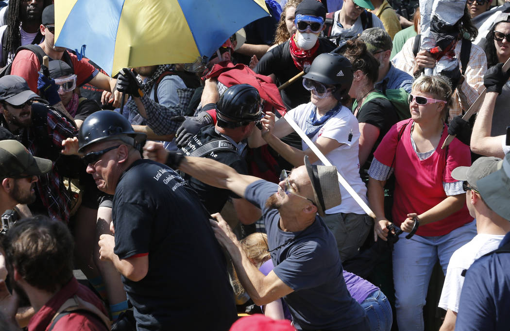 In this Aug. 12, 2017 file photo, white nationalist demonstrators clash with counter demonstrators at the entrance to Lee Park in Charlottesville, Va. A former federal prosecutor says the law enfo ...