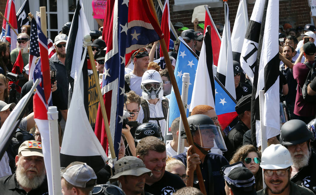 In this Saturday, Aug. 12, 2017, file photo, white nationalist demonstrators walk into the entrance of Lee Park surrounded by counter demonstrators in Charlottesville, Va.  A former federal prosec ...