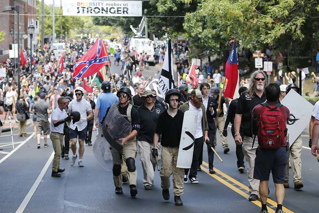 In this Aug. 12, 2017 file photo, white nationalist demonstrators walk through town after their rally was declared illegal near Lee Park in Charlottesville, Va. A former federal prosecutor says th ...