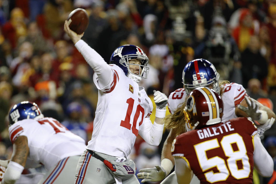New York Giants quarterback Eli Manning (10) passes the ball during the first half of an NFL football game against the Washington Redskins in Landover, Md., Thursday, Nov. 23, 2017. (AP Photo/Patr ...
