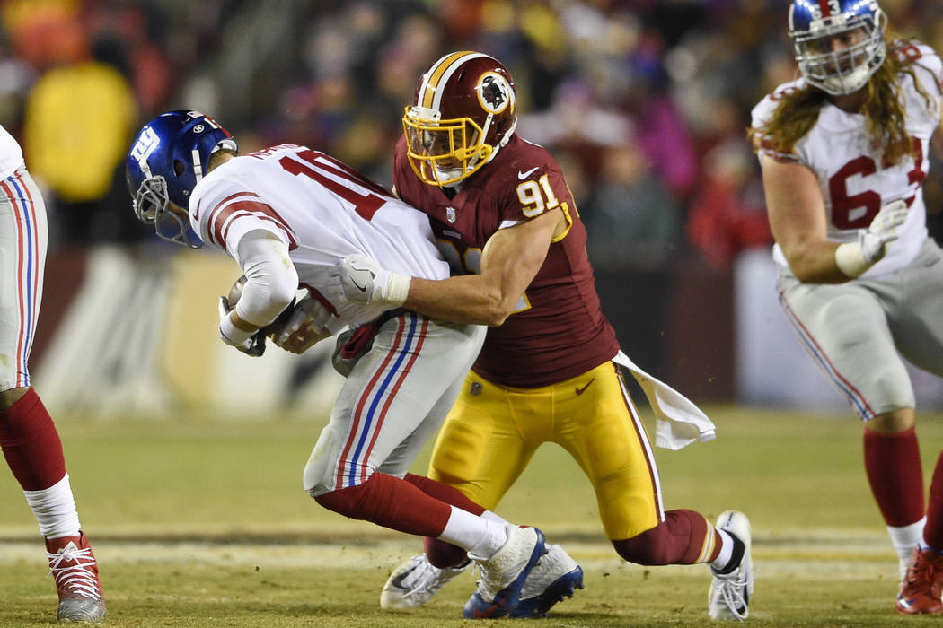 Washington Redskins outside linebacker Ryan Kerrigan (91) sacks New York Giants quarterback Eli Manning (10) during the first half of an NFL football game in Landover, Md., Thursday, Nov. 23, 2017 ...