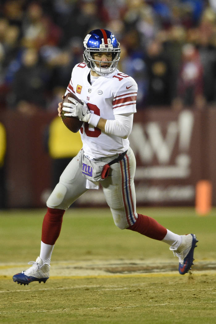 New York Giants quarterback Eli Manning (10) scrambles with the ball during the first half of an NFL football game against the Washington Redskins in Landover, Md., Thursday, Nov. 23, 2017. (AP Ph ...